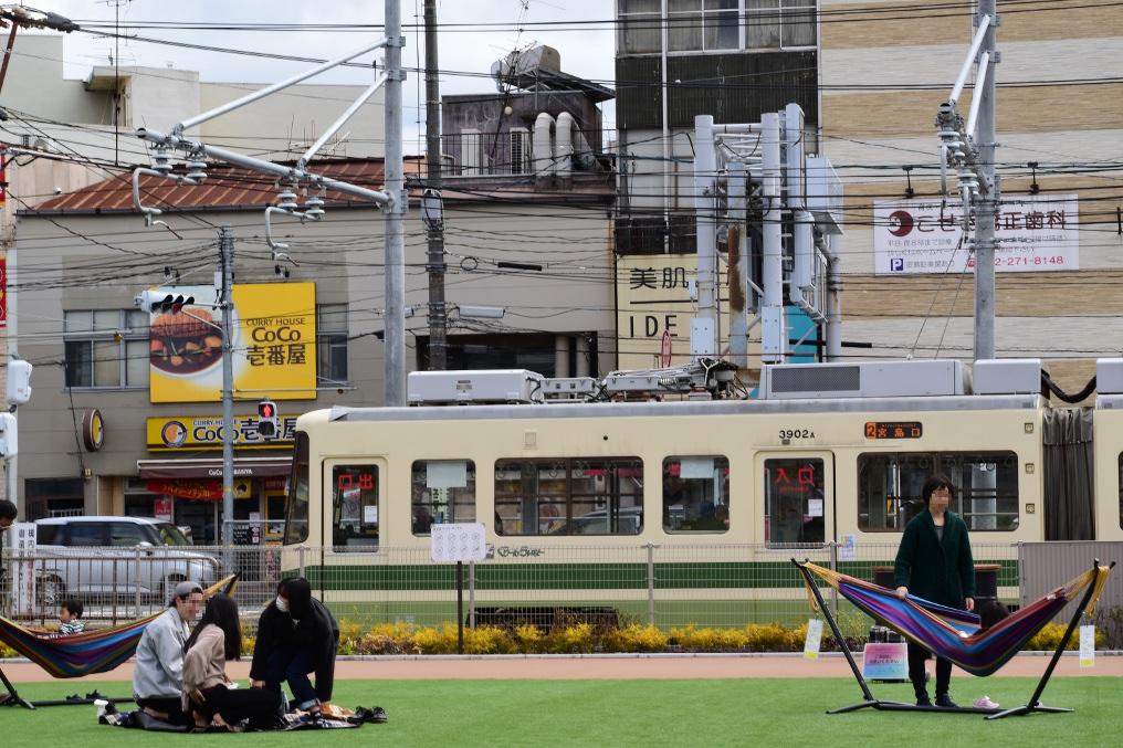 広電西広島駅の芝生でくつろぐ家族連れ
