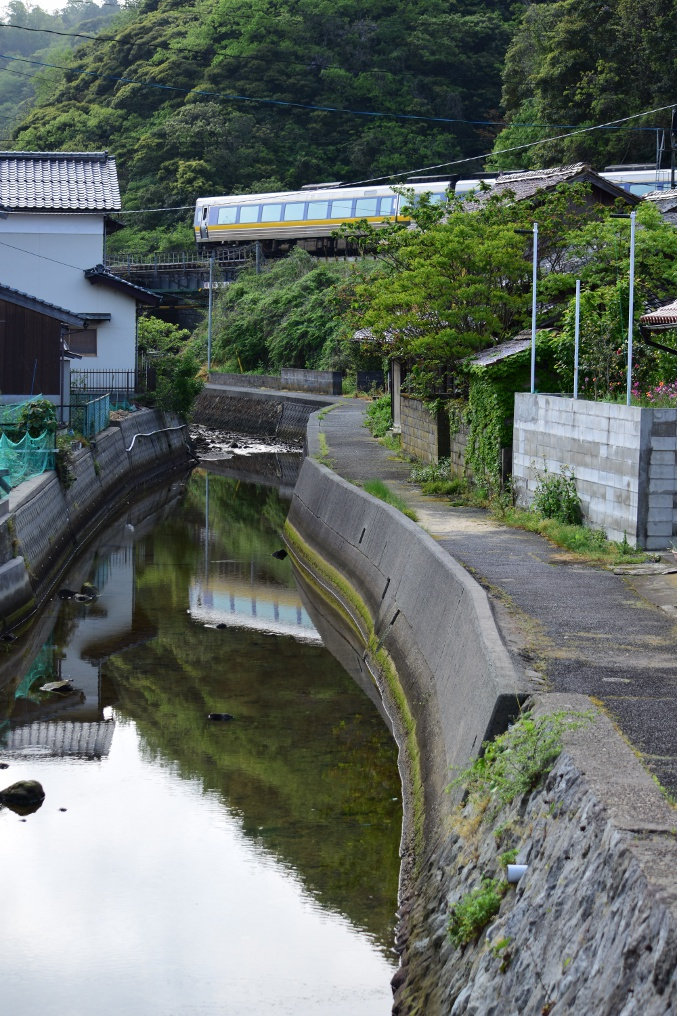 温泉津駅近くの小川の水鏡とJR山陰本線の気動車